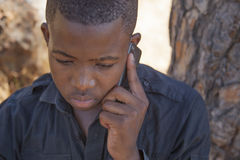 African boy on cell phone. Outside Stock Photo