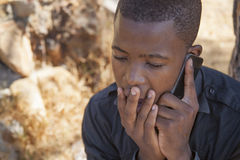 African boy on cell phone. Outside Royalty Free Stock Images