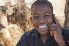African boy on cell phone. Outside Royalty Free Stock Image