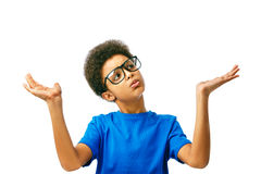 African boy choosing. Shrugging African American boy in doubt doing shrug showing open palms. School boy, teenager with eyeglasses. Boy choosing Isolated, over Royalty Free Stock Photos