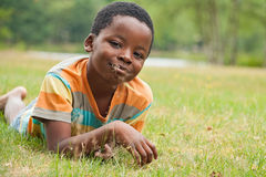 African boy eating grass. African boy is relacing in the grass royalty free stock images