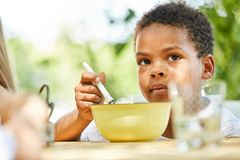 African boy is eating healthy cereal. In international vacation camp Stock Photo