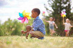 African boy and friends with pinwheels. Playing at the park Royalty Free Stock Images