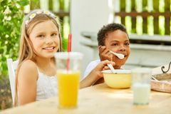 African boy and a girl at breakfast royalty free stock photos