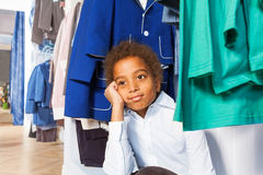 African boy with hand on cheek sits under hangers Royalty Free Stock Photos