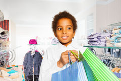 African boy between hangers holds shopping bags Stock Image