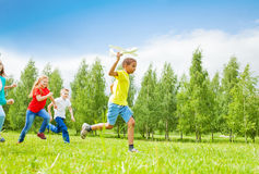 African boy holding airplane toy and kids behind. African boy holding big white airplane toy and children behind running in the field during summer day royalty free stock photography