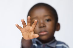 African boy holding his hand out as a STOP sign for racism and abuse. Isolated on white. Little African boy making a facial expression. Here he is making a stop Royalty Free Stock Photography