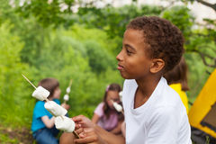 African boy holding stick with marshmallows Royalty Free Stock Photo