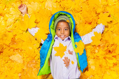 African boy laying in autumn maple leaves Stock Photography
