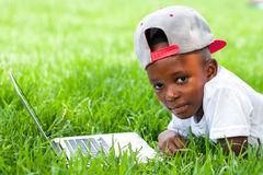 African boy laying with laptop on grass. Royalty Free Stock Photo