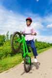 African boy with one wheel of bike up rides it Royalty Free Stock Image