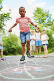 African boy playing hopscotch with ambition Stock Images