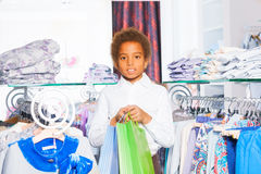 African boy between rows with clothes at store Stock Photo
