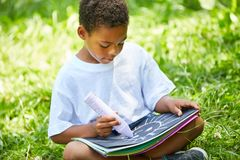 African boy paints a chalk picture in the garden. African boy sits in the garden and paints a chalk image in preschool Royalty Free Stock Images