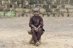 African Boy Sitting Outdoors Portrait. Little african boy sitting on wooden bench and looking at camera with blurred background Stock Photos