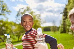 African boy smiles naughty in the park. African boy smiles naughty and drinks water from a water bottle in the park stock photo