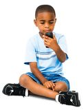 African boy text messaging. On a mobile phone isolated over white Royalty Free Stock Photography