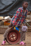 African boy on wheel rim royalty free stock photography