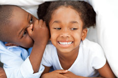 African boy whispering something to his sister. Both lying under a blanket stock images