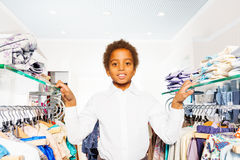 African boy in white shirt stand between hangers Royalty Free Stock Photos