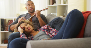 African boyfriend serenading his girlfriend with ukulele royalty free stock photos