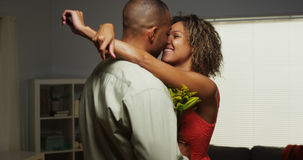 African boyfriend surprises girlfriend with flowers. In living room Stock Photos