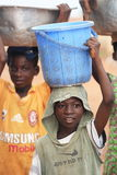 African boys carrying boxes with food on heads Stock Photography