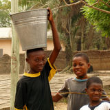 African boys taking water - Ghana. Three young african boys taking water with a bucket - Ghana stock image