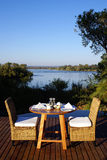 African Breakfast. A small table and two chairs set up for breakfast in the African Outdoors, overlooking the river leading to the Victoria Waterfalls stock photography