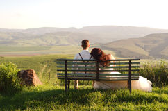 African bride and groom on bench with landscape Stock Photo