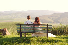 African bride and groom on bench with landscape. Bride and groom outside garden wedding on bench with African Natal Midlands mountain scenery background Royalty Free Stock Image
