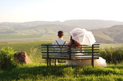 African bride and groom on bench with landscape. Bride and groom outside garden wedding on bench with African Natal Midlands mountain scenery background Stock Image
