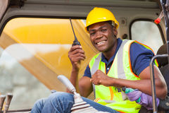 African bulldozer operator. Cheerful african bulldozer operator talking on walkie talkie on construction site Stock Photography