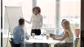 African business coach consulting team working with whiteboard at training. Mixed race business women manager coach mentor consulting diverse team work on stock photos