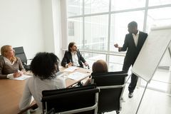 African business coach gives presentation for team at board meet. African business coach gives presentation at board meeting working with flipchart, executive Stock Photography