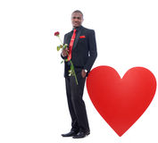 African business man posing and leaning of big heart. Portrait of handsome african man holding red rose, romantic present for Valentine day, posing and smiling Stock Photography