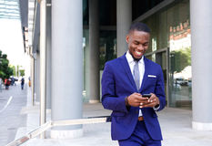 African business man walking and looking at mobile phone Royalty Free Stock Photography