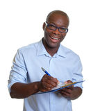 African business man writing notes on a clipboard Royalty Free Stock Photos