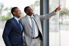 African business men pointing. Happy african business men pointing in modern office stock photo