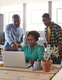 African business team using a laptop together in an office. Casually dressed young African entrepreneurs working on a laptop together while standing at a table stock photo