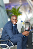 African business traveller. Happy male african business traveller in airport waiting for flight Stock Photo