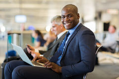 African business traveller. Happy african business traveller with laptop computer at airport Royalty Free Stock Image