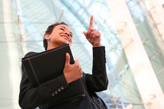 African Business Woman. A pretty african american business woman at her company pointing Stock Images