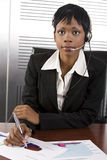 African Business Woman. Young attractive african call center agent talking on the headset in a modern office setting Royalty Free Stock Photo