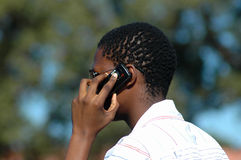 African businessman. An African young businessman holding his mobile cellphone in his black hand and phoning in a park outdoors in South Africa. He is at work Stock Image