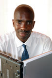 African businessman. Sitting in front of a laptop on its side Stock Photo