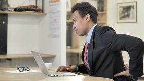 African Businessman with Back Pain working on Laptop stock footage