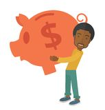 African businessman carries a big piggy bank for Stock Photography