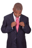 African businessman correcting a tie Royalty Free Stock Photos